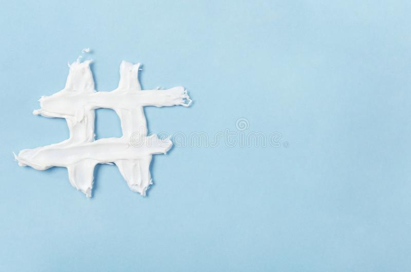 Hashtag από την άσπρη κρέμα προσώπου σε ένα μπλε υπόβαθρο Έννοια της τεχνολογίας, επικοινωνία, on-line εμπορικός, βιομηχανία ομορ στοκ εικόνες