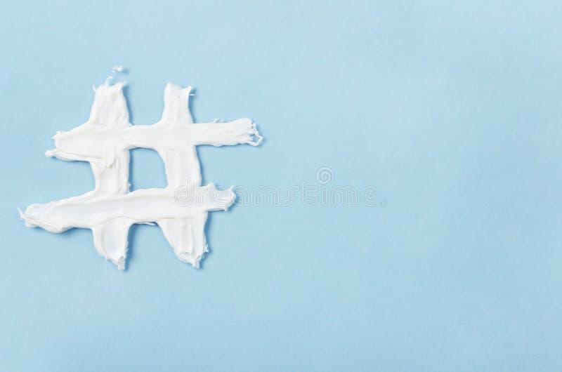 Hashtag de la crème de visage blanche sur un fond bleu Concept de technologie, communication, vente en ligne, industrie de beauté photo stock