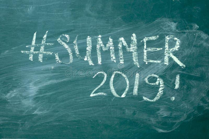 Hashtag 2019 do verão ele escrito à mão com giz branco em um quadro-negro verde imagem de stock royalty free