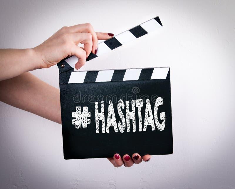 Hashtag Mains femelles tenant le clapet de film images stock
