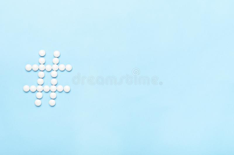 A hashtag of pills on a blue background. Concept medicine, health, technology, online treatment. Copy space, top view royalty free stock photo