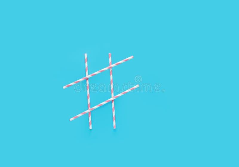 Hashtag tecken som göras från randiga dricka sugrör för rosa färger och för vitbok på ljust - blå bakgrund Gyckel för beröm för f arkivbild