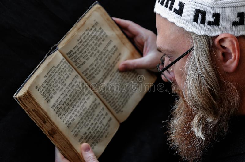 A Hasidic Jew reads Siddur. Religious orthodox Jew with a red beard and with pace in a white bale. Praying. On the bale is an inscription Rabbi Nahman from Uman stock image