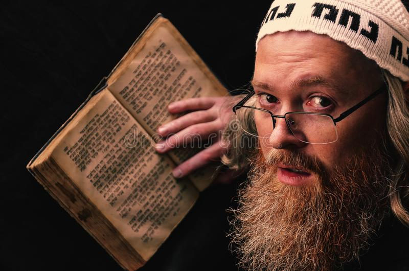 A Hasidic Jew reads Siddur. Religious orthodox Jew with a red beard and with pace in a white bale praying. Closeup. A Hasidic Jew reads Siddur. Religious stock photo