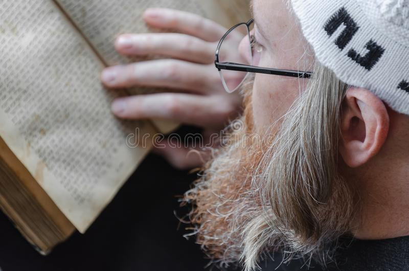 A Hasidic Jew reads Siddur. Religious orthodox Jew with a red beard and with pace in a white bale praying. Closeup. A Hasidic Jew reads Siddur. Religious royalty free stock images