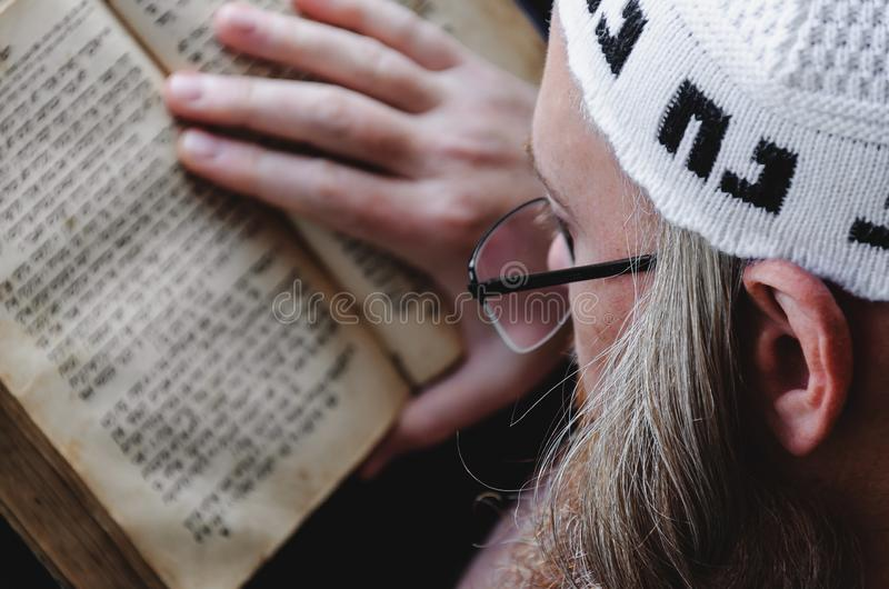 A Hasidic Jew reads Siddur. Religious orthodox Jew with a red beard and with pace in a white bale praying. Closeup. A Hasidic Jew reads Siddur. Religious royalty free stock photos
