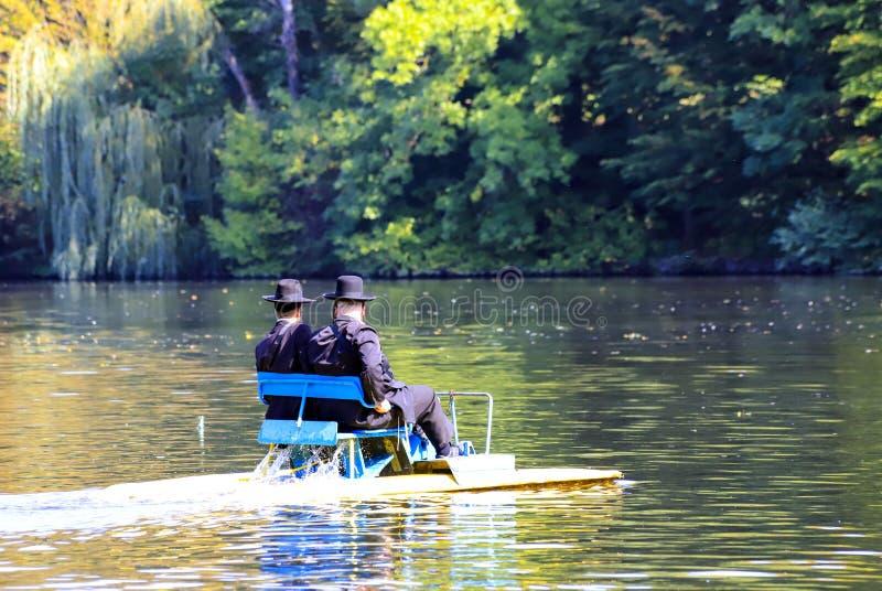 2 Hasidic Joden berijden een catamaran op het meer in het de herfstpark in Uman, de Oekraïne, tijdens het Joodse Nieuwjaar stock foto's