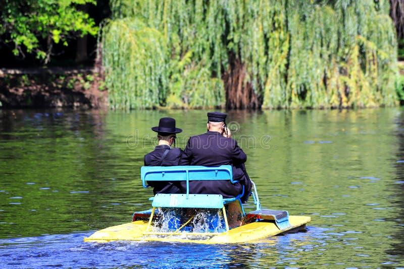2 Hasidic Juden in der traditionellen schwarzen Kleidung reiten ein Katamaran auf den See im Herbst Sophia Park in Uman, Ukraine, lizenzfreies stockfoto
