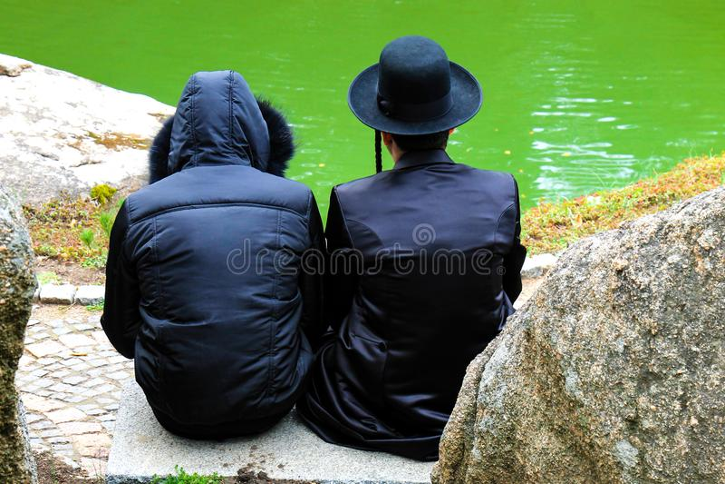 2 Hasidic mężczyzna, Żydowska rodzina w tradycyjnych ubraniach czytających modlitwę w parku w Uman, Ukraina czas Żydowski Nowy Ye zdjęcia stock