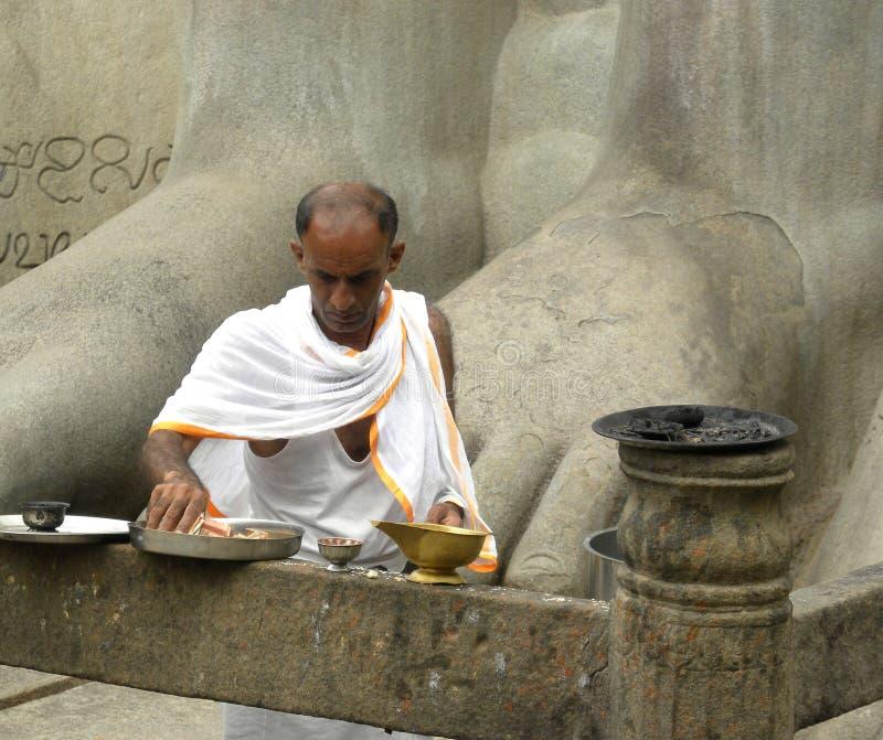 Hassan Karnataka, Indien - September 12, 2009 Jain präst nära forntida, monolitisk staty för granit av Lord Gommateshwara royaltyfri fotografi