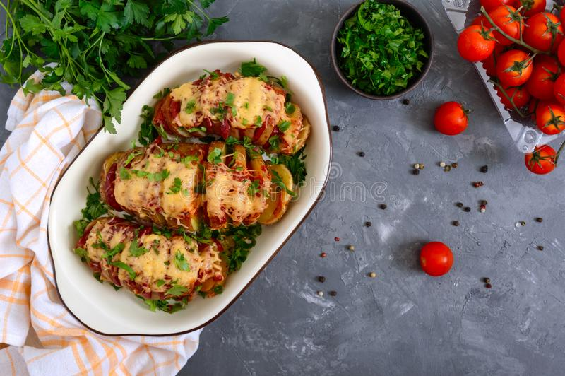 Hasselback potato stuffed with salami, cheese, ketchup, garlic and herbs. Baked whole potatoes is sliced and stuffed. Traditional stock images