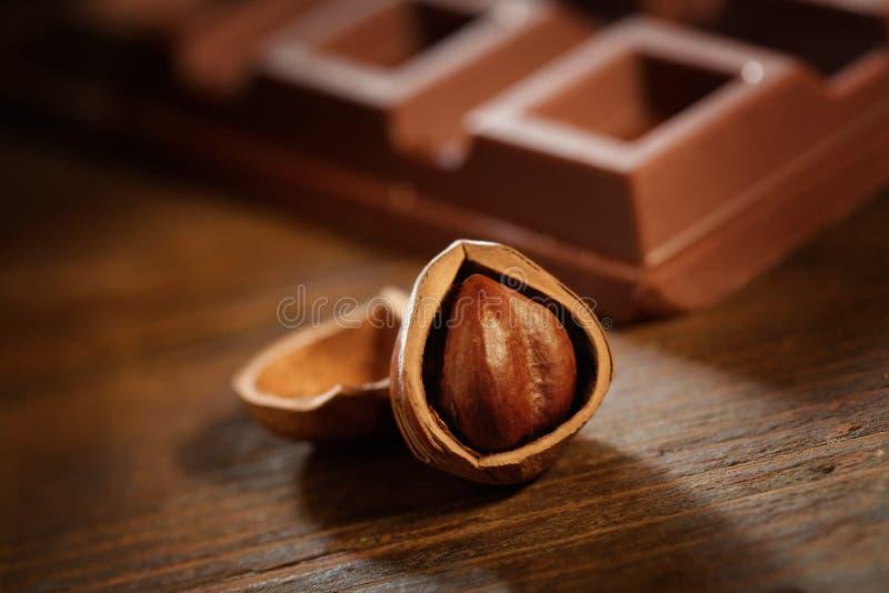 Hasselnöt med chokladstången på den lantliga trätabellen fotografering för bildbyråer