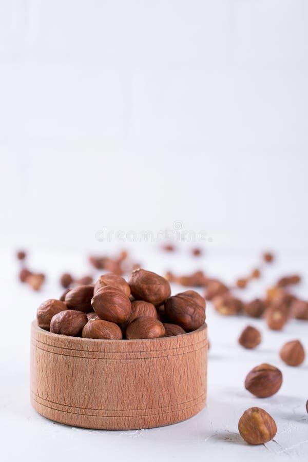 Hasselnötter i brun träbunke på vit arkivfoto