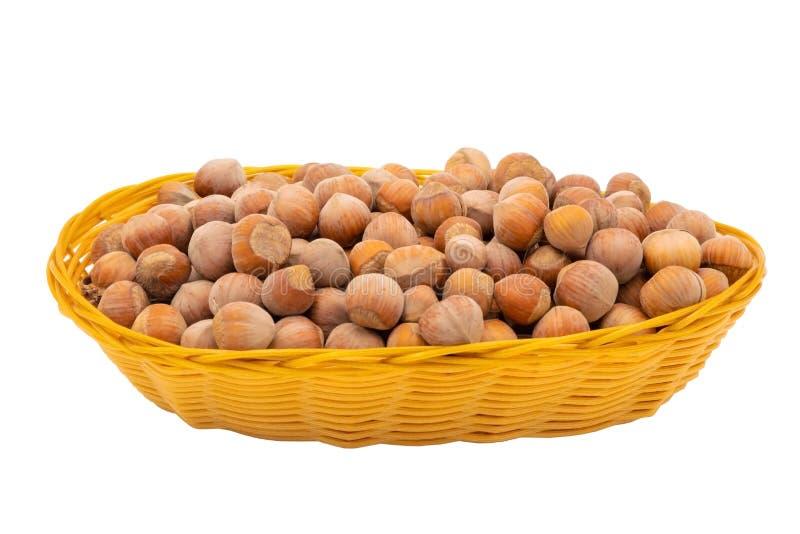 Hasselnötter i en vide- korg På vitbakgrund arkivfoton