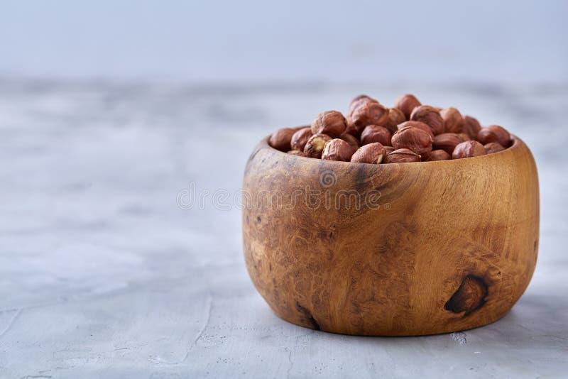Hasselnötter i keramisk bunke på wihitebakgrund med kopieringsutrymme, bästa sikt, selektiv fokus royaltyfri foto