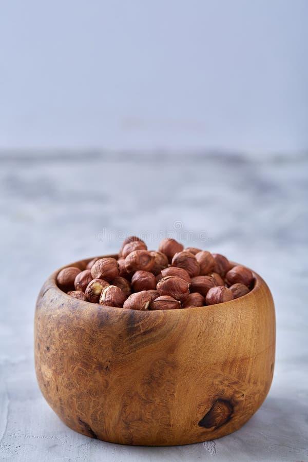 Hasselnötter i keramisk bunke på wihitebakgrund med kopieringsutrymme, bästa sikt, selektiv fokus royaltyfria bilder