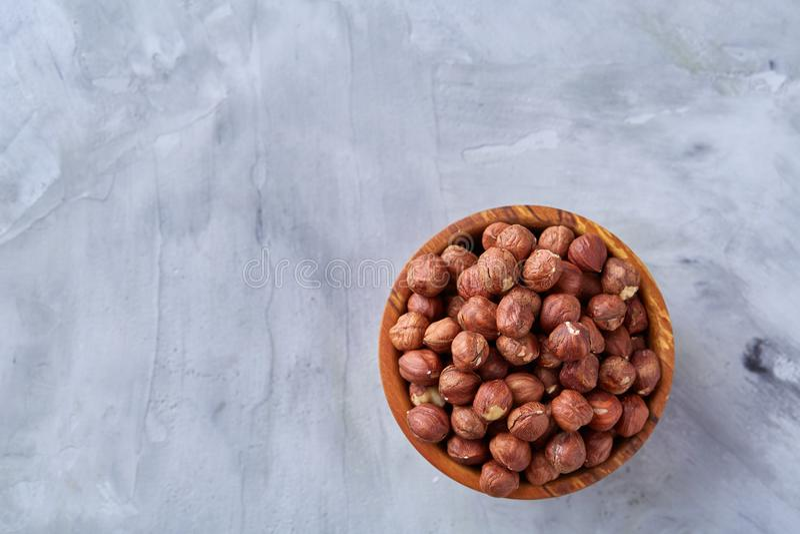 Hasselnötter i keramisk bunke på wihitebakgrund med kopieringsutrymme, bästa sikt, selektiv fokus arkivbilder
