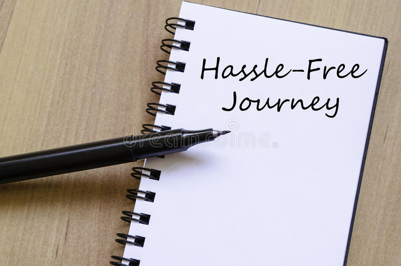 Hassle free journey write on notebook. Hassle free journey text concept write on notebook with pen royalty free stock photography
