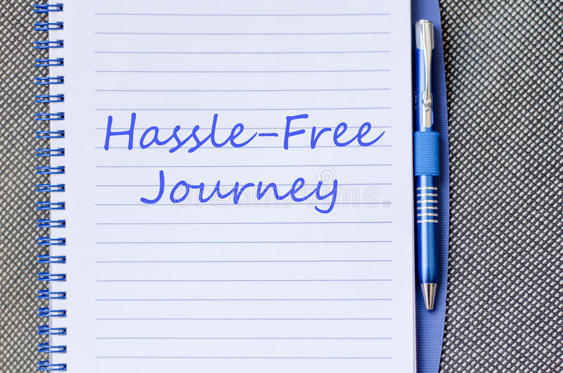 Hassle free journey write on notebook. Hassle free journey text concept write on notebook with pen royalty free stock photo