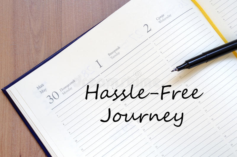 Hassle free journey write on notebook. Hassle free journey text concept write on notebook with pen royalty free stock photos