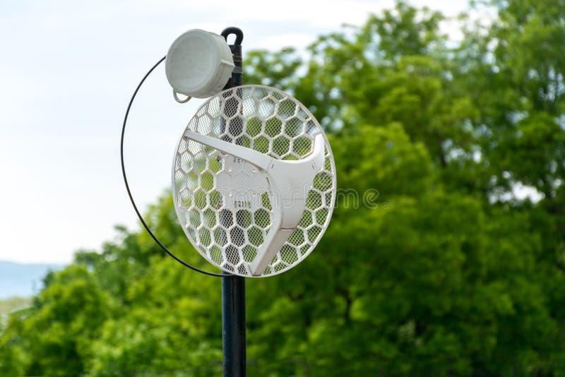 Haste de metal sem fio exterior da antena do Internet no telhado e na árvore verde e céu no fundo fotografia de stock