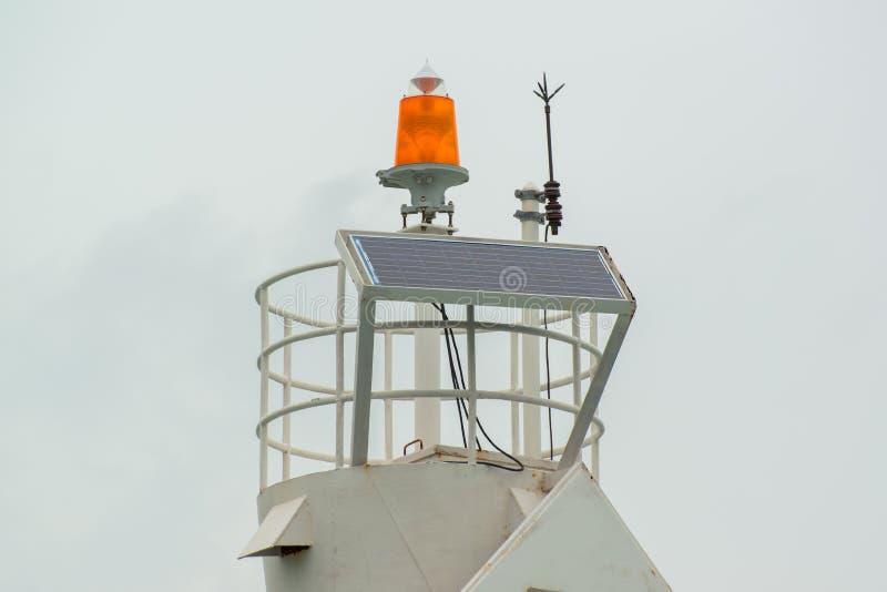 Haste de relâmpago e solarcell na parte superior do farol no porto imagens de stock royalty free