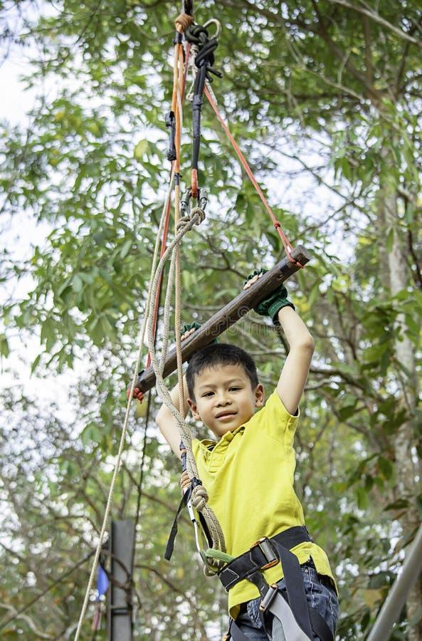 Haste de suspensão do menino do Asean amarrada com cordas e a árvore obscura do fundo dos estilingues imagens de stock