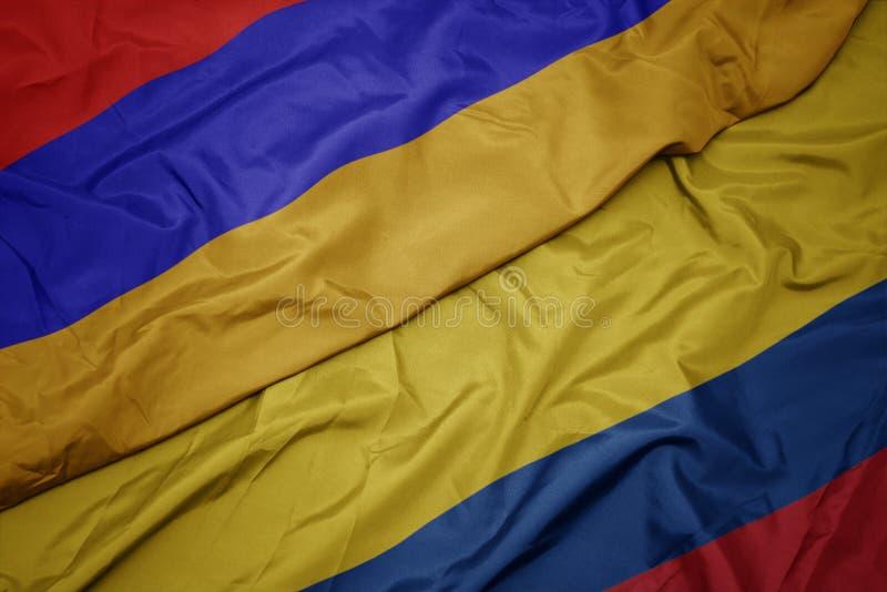 hasteando bandeira colorida da colômbia e bandeira nacional da armênia imagem de stock