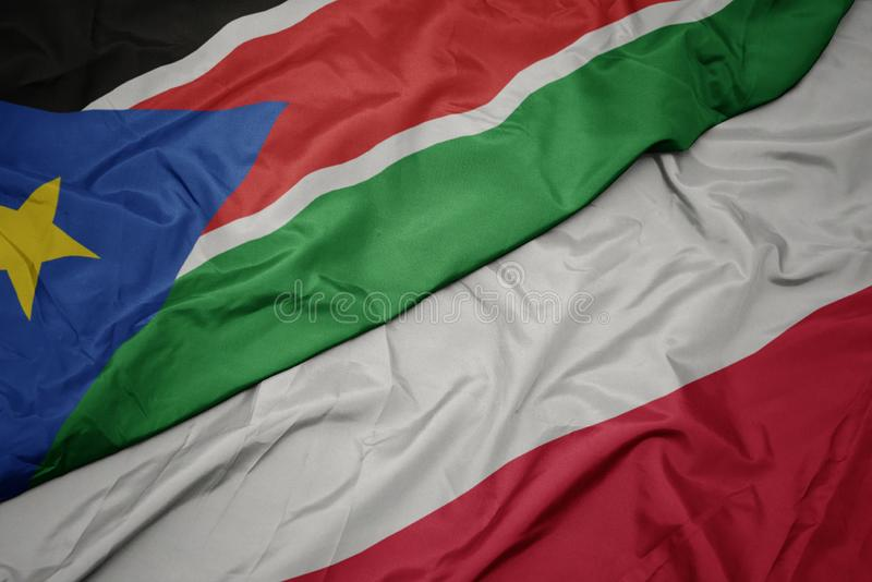 hasteando bandeira colorida da polônia e bandeira nacional do sudão do sul fotografia de stock