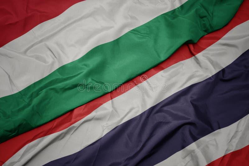 hasteando bandeira colorida da tailândia e bandeira nacional da hungria foto de stock royalty free