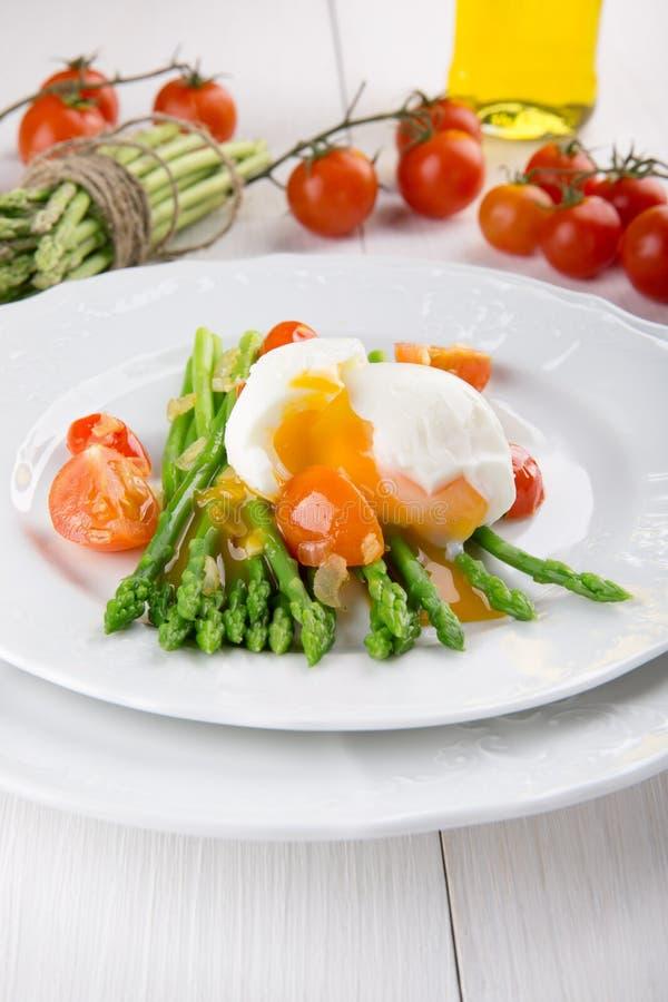 Hastes verdes do aspargo com ovo quente, tomate e molho foto de stock