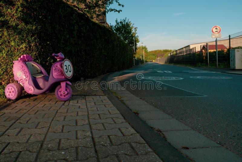 Hastighetsbegränsningtecken av 30 i form av rosa barns ritt på medlet arkivbild