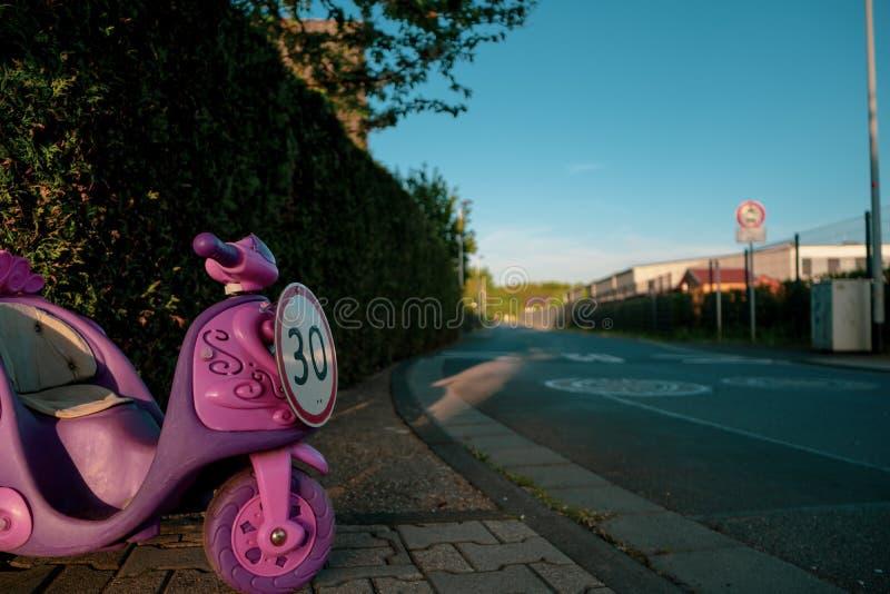 Hastighetsbegränsningtecken av 30 i form av rosa barns ritt på medlet royaltyfri fotografi