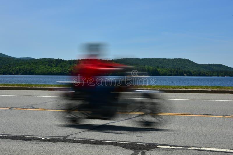Hastighetsbegrepp - motorcykel som rusar den förgångna sjön royaltyfria bilder