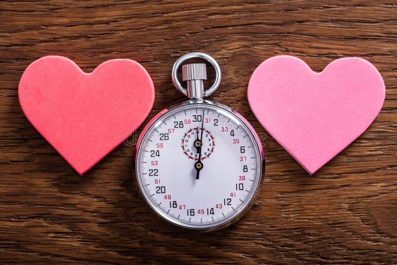 Hastighetsdatummärkningbegrepp Hjärtor och en stoppur fotografering för bildbyråer