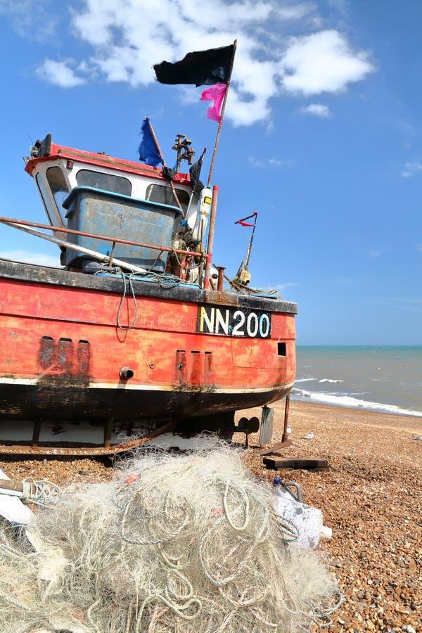 HASTINGS, ВЕЛИКОБРИТАНИЯ - 27-ОЕ ИЮНЯ 2015: Пляж запустил рыбацкую лодку с рыболовной сетью на переднем плане стоковые изображения rf