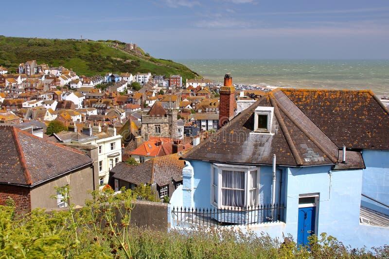 HASTINGS, HET UK: Algemene mening van de oude stad van Hastings van het Westenheuvel met groene heuvels en het overzees op de ach stock fotografie