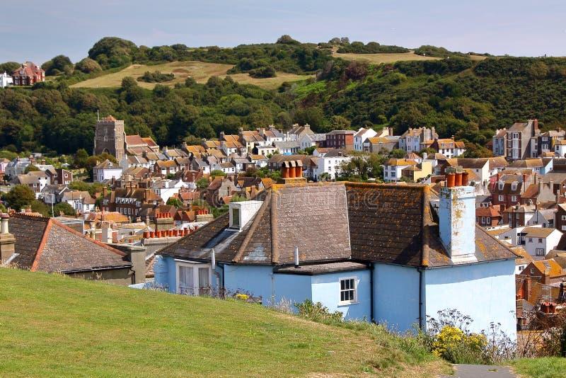 HASTINGS, UK: Γενική άποψη της παλαιάς πόλης Hastings από το δυτικό Hill με τους πράσινους λόφους και της θάλασσας στο υπόβαθρο στοκ φωτογραφίες με δικαίωμα ελεύθερης χρήσης