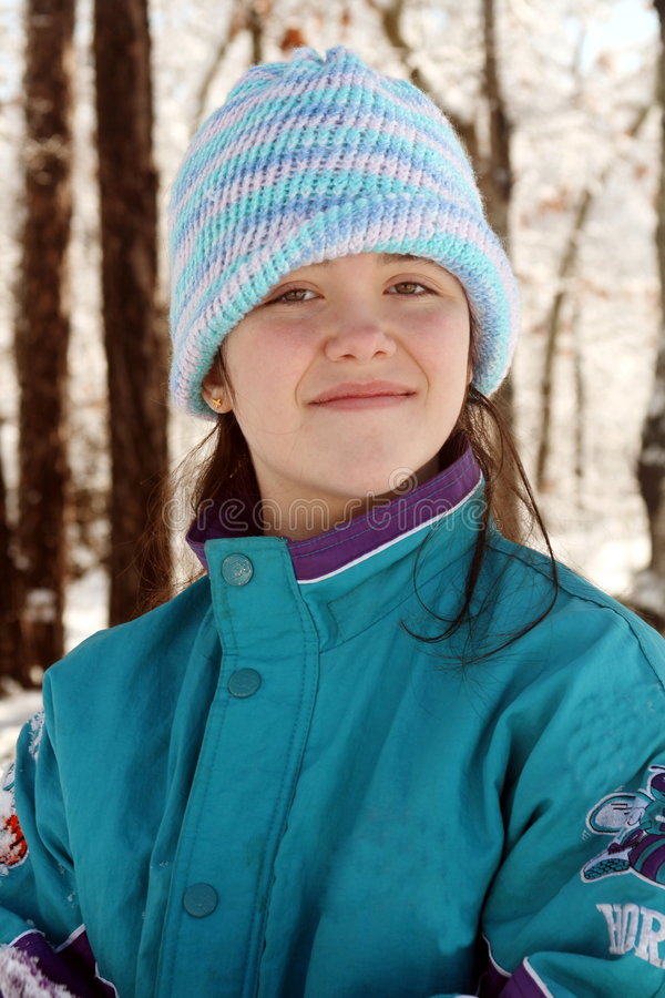 Teen in beanie hat. Young teenage girl outside in winter wears a blue coat and striped wool beanie hat stock images