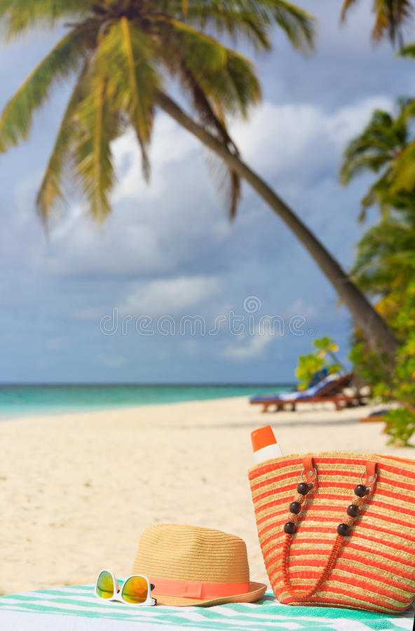 Hat, bag, sun glasses and flip flops on the beach royalty free stock photography
