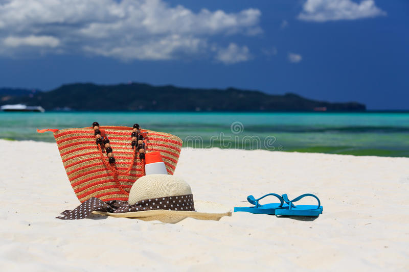 Hat, bag, sun glasses and flip flops on tropical beach royalty free stock photo