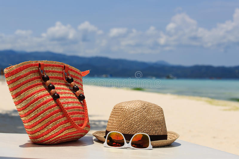 Hat, bag, sun glasses and flip flops on tropical beach stock image
