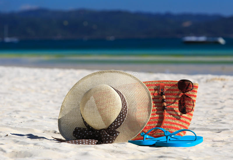 Hat, bag, sun glasses and flip flops on tropical beach stock photo
