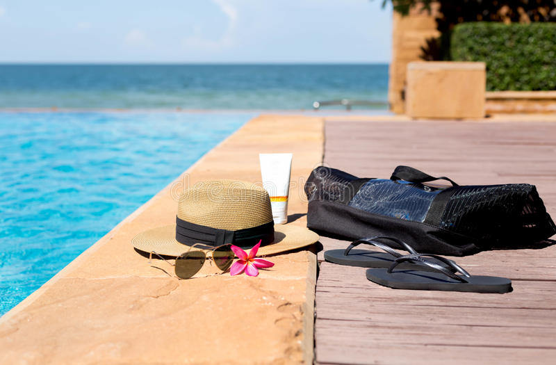 Hat, beach bag, sunglasses and flip flops next to swimming pool. With beach background stock image