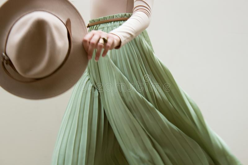 Hat, beige blouse and turqoise pleats skirt on light street backgraund. royalty free stock photo