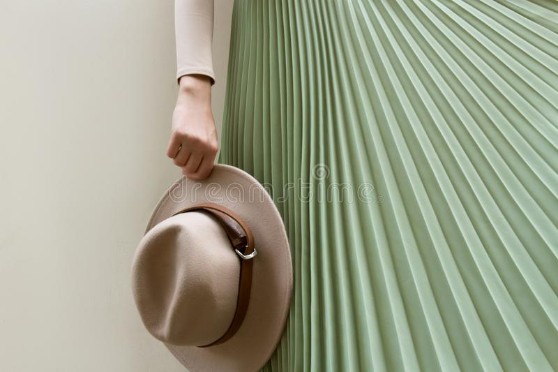Hat, beige blouse and turqoise pleats skirt on light street backgraund. stock images