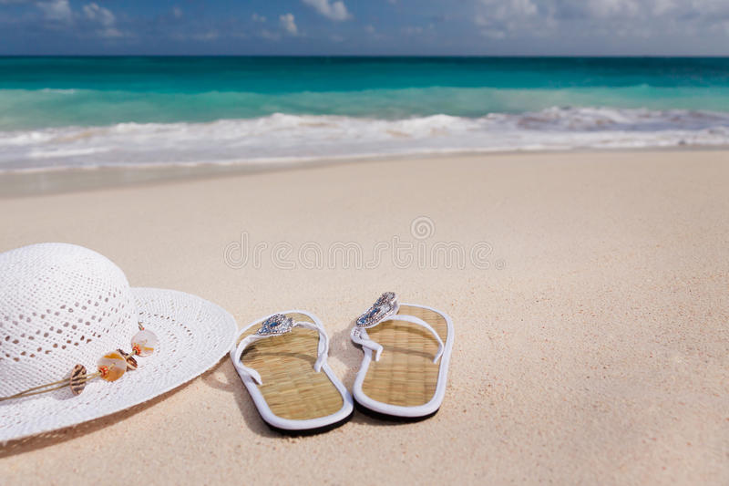 Hat and flip-flops on the beach. White hat and flip-flops on the beach with blue sea in the background royalty free stock photos