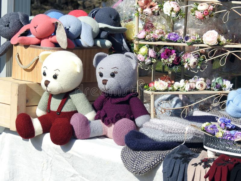 Hat, flowers and bear toys in market, Latvia. Hat, flowers and colorful bear toys in street market stock image