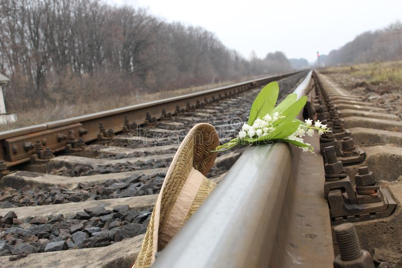 Hat and flowers lies on the train rails. Dangers on the railway track royalty free stock photo