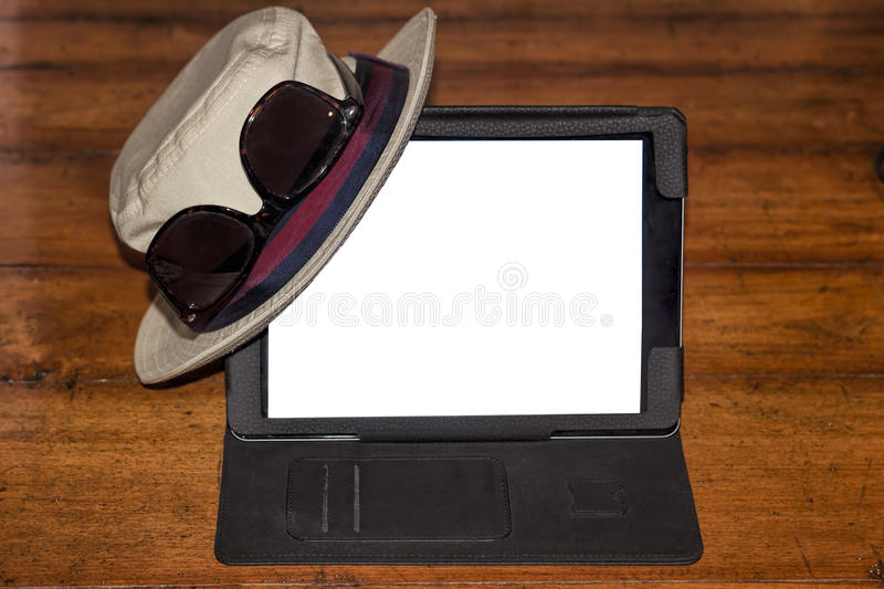 Hat and glasses on a digital tablet. Fedora and sunglasses on a digital tablet stock photography